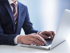 ノートパソコンを操作する男性の写真